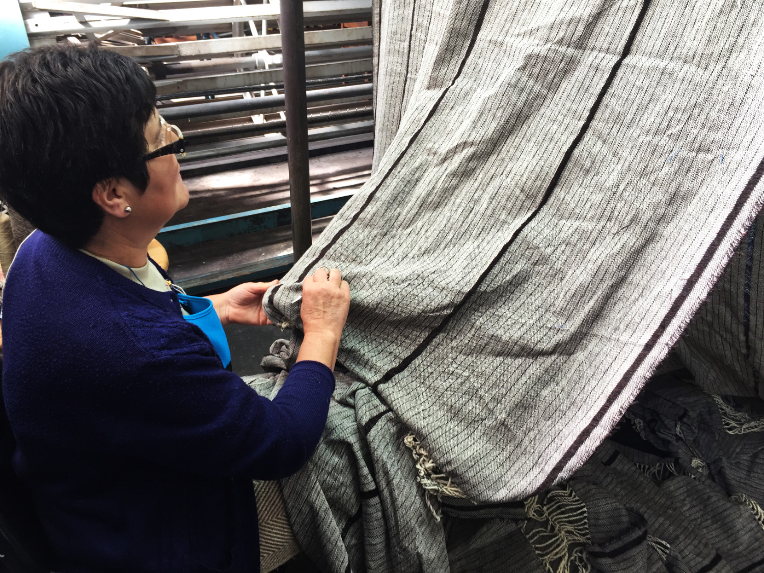 A woman checks each scarf for flaws and repairs them by hand