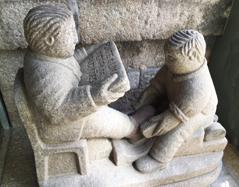Granite carving of a shoeshine boy and his client