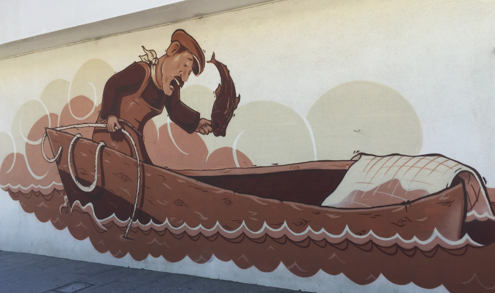 Humorous wall painting of a fisherman on the wall of the Tourism Office.